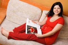 Schöne schwangere Frau, die auf der Couch sitzt Lizenzfreies Stockfoto