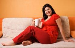 Schöne schwangere Frau, die auf der Couch sitzt Stockfoto