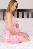 Schöne schwangere Frau, die auf einem Bett in einem Kleid sitzt Stockfoto