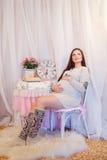 Schöne schwangere Frau, die auf einem Stuhl sitzt und Stockfotos