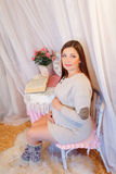 Schöne schwangere Frau, die auf einem Stuhl sitzt und Lizenzfreies Stockbild