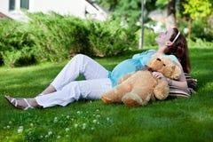 Schöne schwangere Frau, die auf grünem Gras sich entspannt Lizenzfreie Stockfotografie