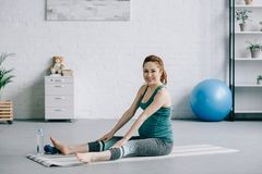 schöne schwangere Frau, die auf Yogamatte ausdehnt und Kamera betrachtet stockfotos