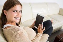 Schöne schwangere Frau, die das Netz surft Lizenzfreies Stockbild