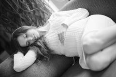 Schöne schwangere Frau, die an der Couch sitzt Stockfotos
