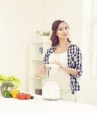 Schöne schwangere Frau, die in der Küche kocht Stockfoto