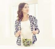 Schöne schwangere Frau, die in der Küche kocht Lizenzfreies Stockfoto