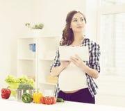Schöne schwangere Frau, die in der Küche kocht Stockfotos