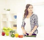 Schöne schwangere Frau, die in der Küche kocht Stockfotografie