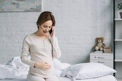 schöne schwangere Frau, die durch Smartphone spricht stockbild