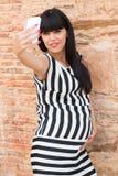 Schöne schwangere Frau, die ein selfie mit Mobile macht Stockbilder