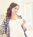 Schöne, schwangere Frau, die einen Tee in der Küche trinkt Mutterschaft, p Lizenzfreie Stockfotos