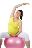 Schöne schwangere Frau, die einige körperliche Bewegungen tut Stockbild