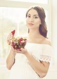 Schöne schwangere Frau, die Erdbeeren in der Küche isst Motherh Lizenzfreie Stockbilder
