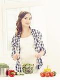 Schöne schwangere Frau, die Frühstück in der Küche zubereitet Motherh Lizenzfreie Stockfotos