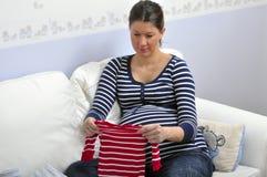 Schöne schwangere Frau, die Kleidung des Schätzchens wählt Stockbilder
