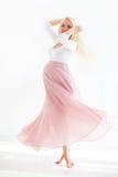 Schöne schwangere Frau, die mit Glück, im hübschen Blumenkleid wirbelt stockfotos