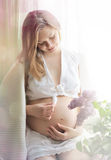 Schöne schwangere Frau, die nahe Fenster sitzt. Lizenzfreies Stockbild