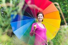 Schöne schwangere Frau, die unter bunten Regenschirm geht Stockbilder