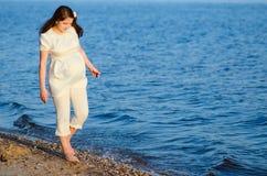 Schöne schwangere Frau geht entlang das Ufer lizenzfreie stockfotos