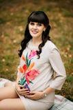 Schöne schwangere Frau hält Bauch im Herbstpark Lizenzfreie Stockbilder