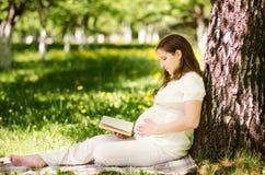 Schöne schwangere Frau im Park mit Buch stockbild