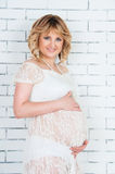 Schöne schwangere Frau im weißen Kleid, das Bauch umarmt Stockfotos