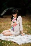 Schöne schwangere Frau ist, schauend sitzend und reizend auf Bauch Stockbild