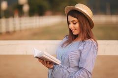 Schöne schwangere Frau las das Buch auf dem Bauernhof Sie steht das fance bereit und schaut herein zum Buch relax lizenzfreie stockbilder