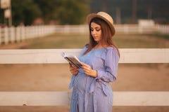 Schöne schwangere Frau las das Buch auf dem Bauernhof Sie steht das fance bereit und schaut herein zum Buch relax stockbilder