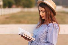 Schöne schwangere Frau las das Buch auf dem Bauernhof Sie steht das fance bereit und schaut herein zum Buch relax lizenzfreies stockfoto