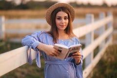 Schöne schwangere Frau las das Buch auf dem Bauernhof Sie steht das fance bereit und schaut herein zum Buch relax stockbild