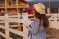 Schöne schwangere Frau las das Buch auf dem Bauernhof Sie steht das fance bereit und schaut herein zum Buch relax stockfoto