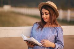 Schöne schwangere Frau las das Buch auf dem Bauernhof Sie steht das fance bereit und schaut herein zum Buch relax lizenzfreie stockfotos