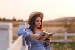 Schöne schwangere Frau las das Buch auf dem Bauernhof Sie steht das fance bereit und schaut herein zum Buch relax stockfotografie