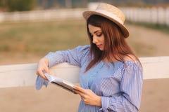 Schöne schwangere Frau las das Buch auf dem Bauernhof Sie steht das fance bereit und schaut herein zum Buch relax lizenzfreies stockbild