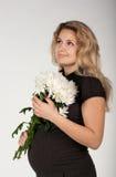 Schöne schwangere Frau mit Blumen Stockfotos