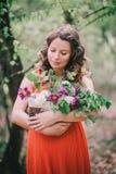 Schöne schwangere Frau mit Blumen im Korb Stockbild