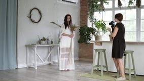 Schöne schwangere Frau mit Blumenstrauß im weißen peignoir, das für weiblichen Fotografen aufwirft Der Fotograf erklärt wie  stock footage