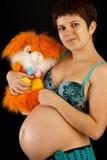Schöne schwangere Frau mit einem Spielzeug Stockfoto