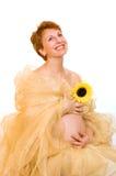 Schöne schwangere Frau mit einer Sonnenblume Lizenzfreie Stockfotos