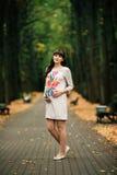 Schöne schwangere Frau steht auf dem gelben Rasen reizend Stockfotografie