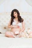 Schöne schwangere Mutter auf Bett in Lotussitz mit Babybeuten Lizenzfreies Stockfoto