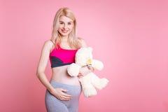 Schöne Schwangerschaft, die ihren Bauch streichelt Stockfotos