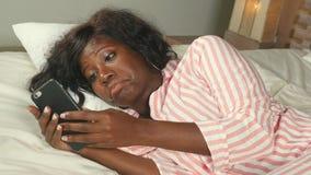 Schöne schwarze afroe-amerikanisch Frau im liegenden entspannten Lächeln der Pyjamas nett und frisch unter Verwendung der Interne stock video footage