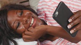 Schöne schwarze afroe-amerikanisch Frau im liegenden entspannten Lächeln der Pyjamas nett und frisch unter Verwendung der Interne stock video