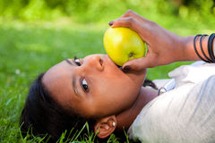 Schöne schwarze Frau, die einen Apfel isst stockfoto