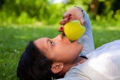Schöne schwarze Frau, die einen Apfel isst Stockfotos