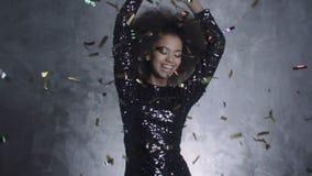 Schöne schwarze Frau, die goldene Konfettis, Zeitlupe wirft stock footage