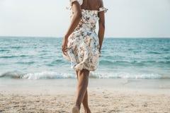 Schöne schwarze Frau, die zum Meer auf dem Strand läuft stockfotografie